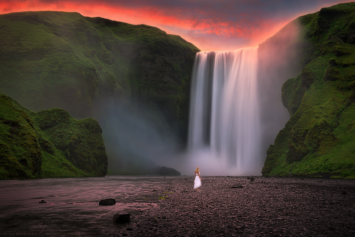 woman standing in front of skogafoss waterfall in iceland